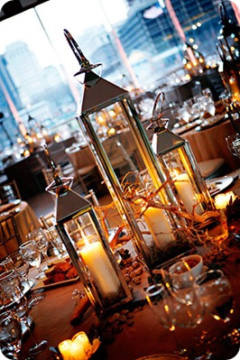 A classic and rustic look with pillar candles in iron lanterns of various heights entwined with branches and rocks