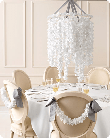Nouveau Romantic Wedding Centerpiece made of white paper doilies suspended over a table and adorning the backs of wooden banquet chairs