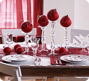 Large red ornaments stacked onto crystal candle holders atop of a red runners