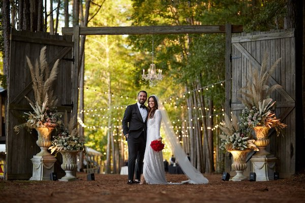 bride and groom standing at the entry doors to their elegant rustic wedding surrounded by tall urns of flowers and grasses