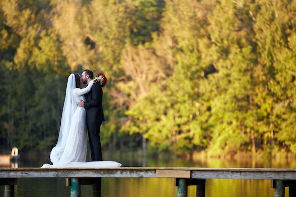 bridrounde and groom standing on a floating dock kissing with fall colored trees in the backg