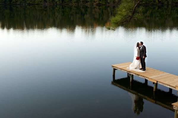 overhead view of a bride and groom standing on a dock in the middle of a lake