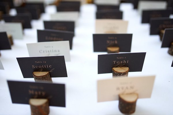 neutral tone custom escort cards sitting in slices of wood