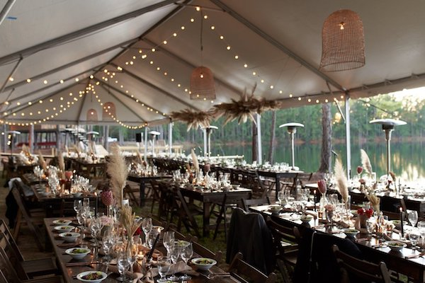 tented wedding reception with twinkle lights, rattan chandeliers, and elegant place settings on wooden farm tables