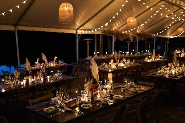 nighttime view of wedding reception with lit rattan chandeliers, twinkle lights and candles