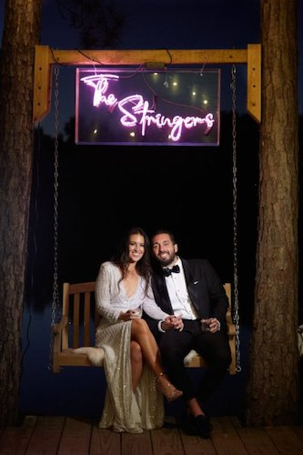 bride and groom sitting on a rustic swing under a neon sign with their last name