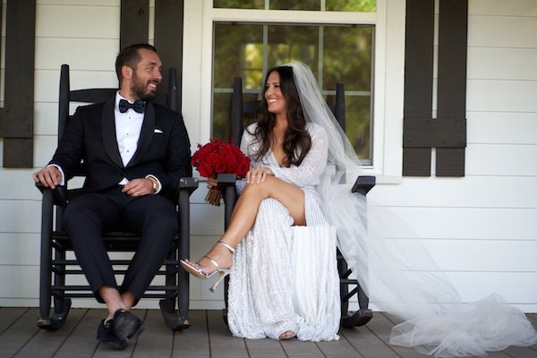 Happy bride and groom sitting on rocking chairs on the front porch of a rustic cabin