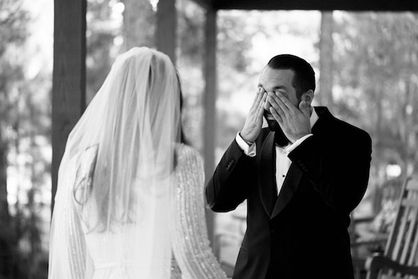 black and white photos of an excited groom wiping away tears after his first look at his bride-to-be