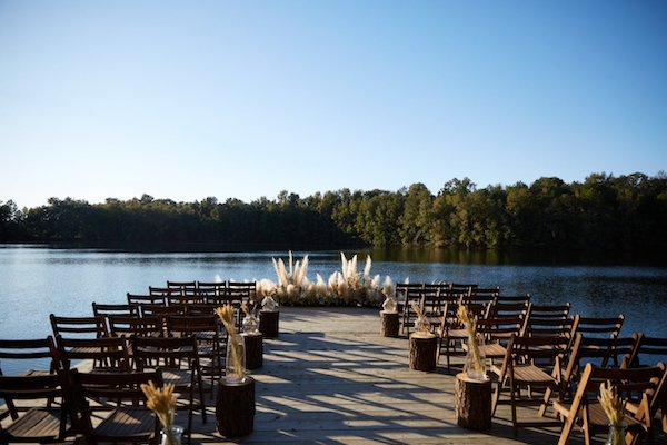 waterfront wedding ceremony on a floating dock, set with rustic grasses and wooden chairs