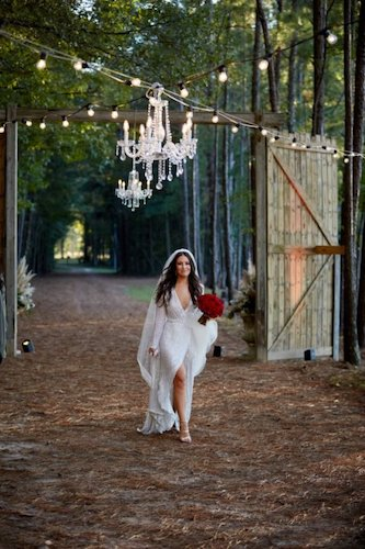 bride in elegant crystal wedding gown walking under crystal chandeliers hanging in the woods