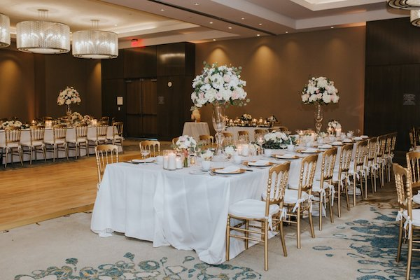 Long tables draped with white linen accented with pink and white flora with gold chairs and accents