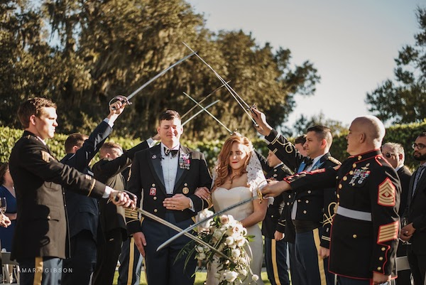 bride and groom under crossed sabers after their Jekyll Island wedding