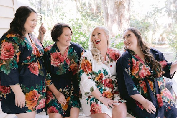bride and bridal party sitting on the front porch wearing floral robes