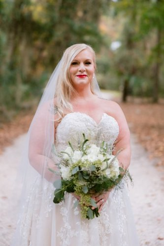 bride wearing white lace wedding gown with a sweetheart neckline carrying a white bouquet