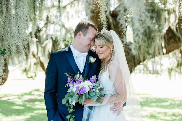 bride and groom standing under trees with hanging Spanish moss