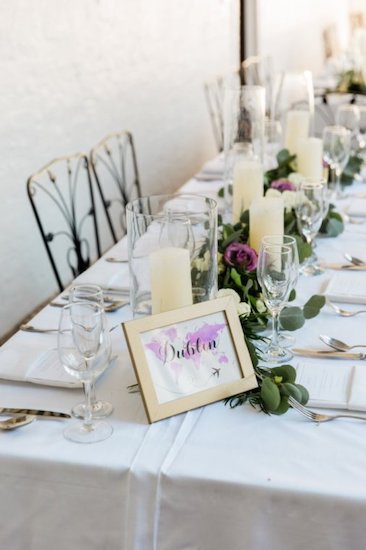 long reception tables draped in white linen with greenery, candles and purple flowers.