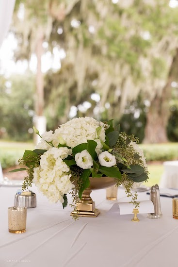 White floral wedding centerpiece with lush greenery for a tented outdoor wedding at Crane Cottage