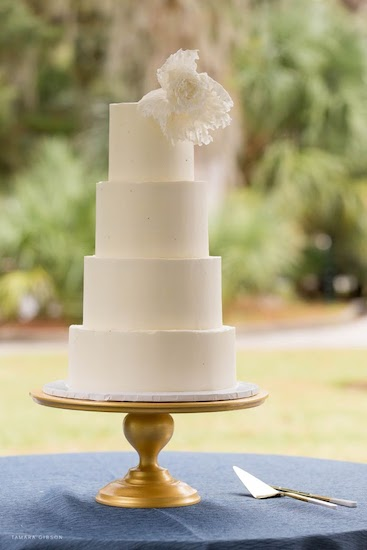 sleek modern four-tiered white wedding cake with a single white peonie