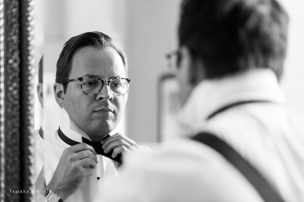 groom looking in the error as he ties his bow tie before his Jekyll Island wedding