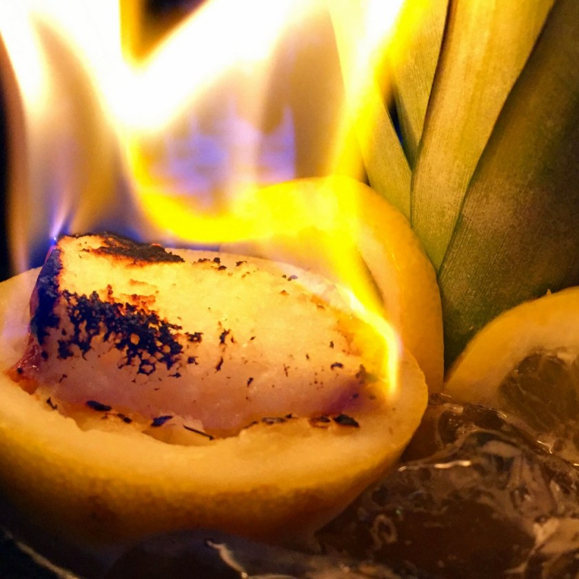 Citrus shell, with bread cube, on fire.