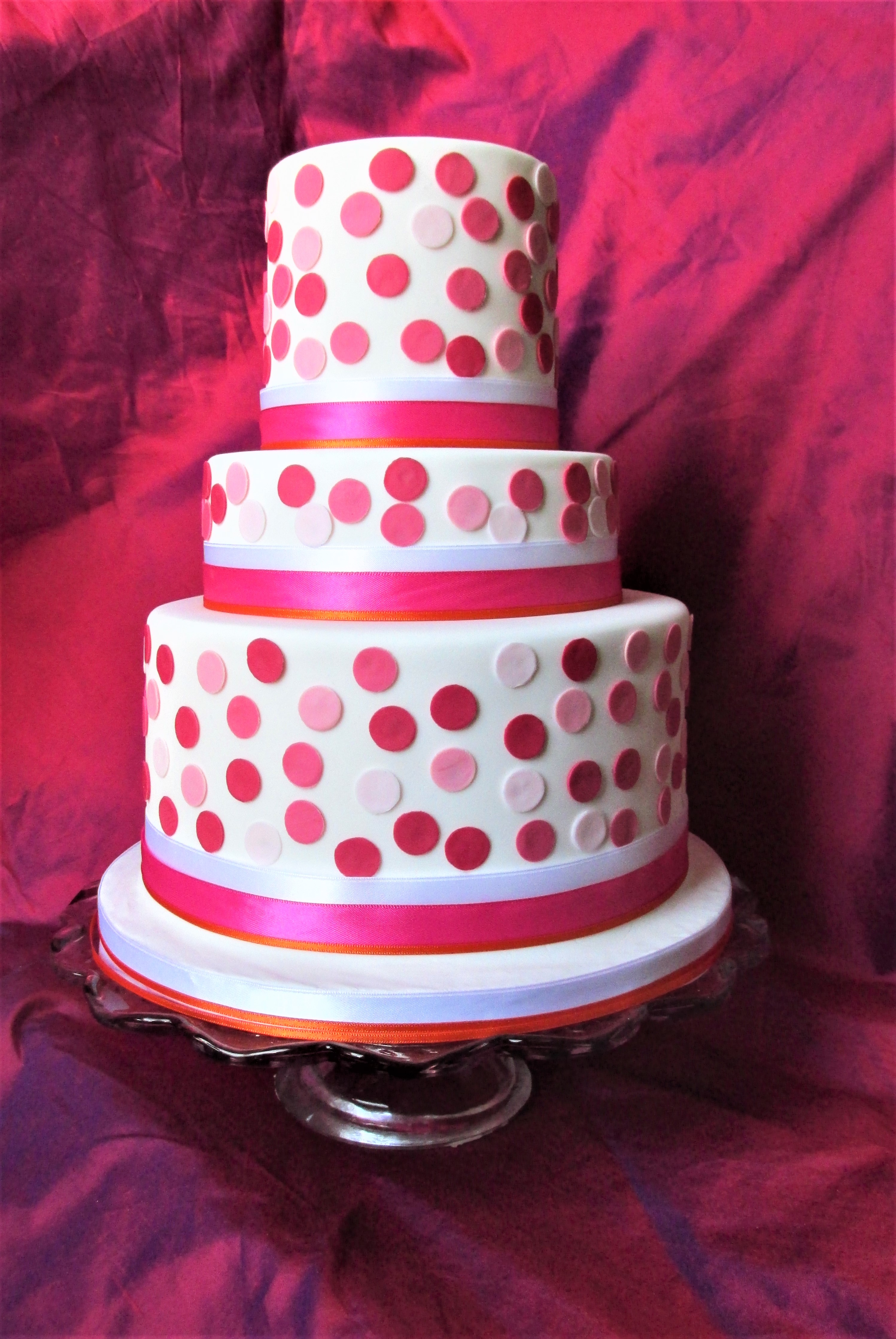 Tiered party cake with pink spots and ribbons