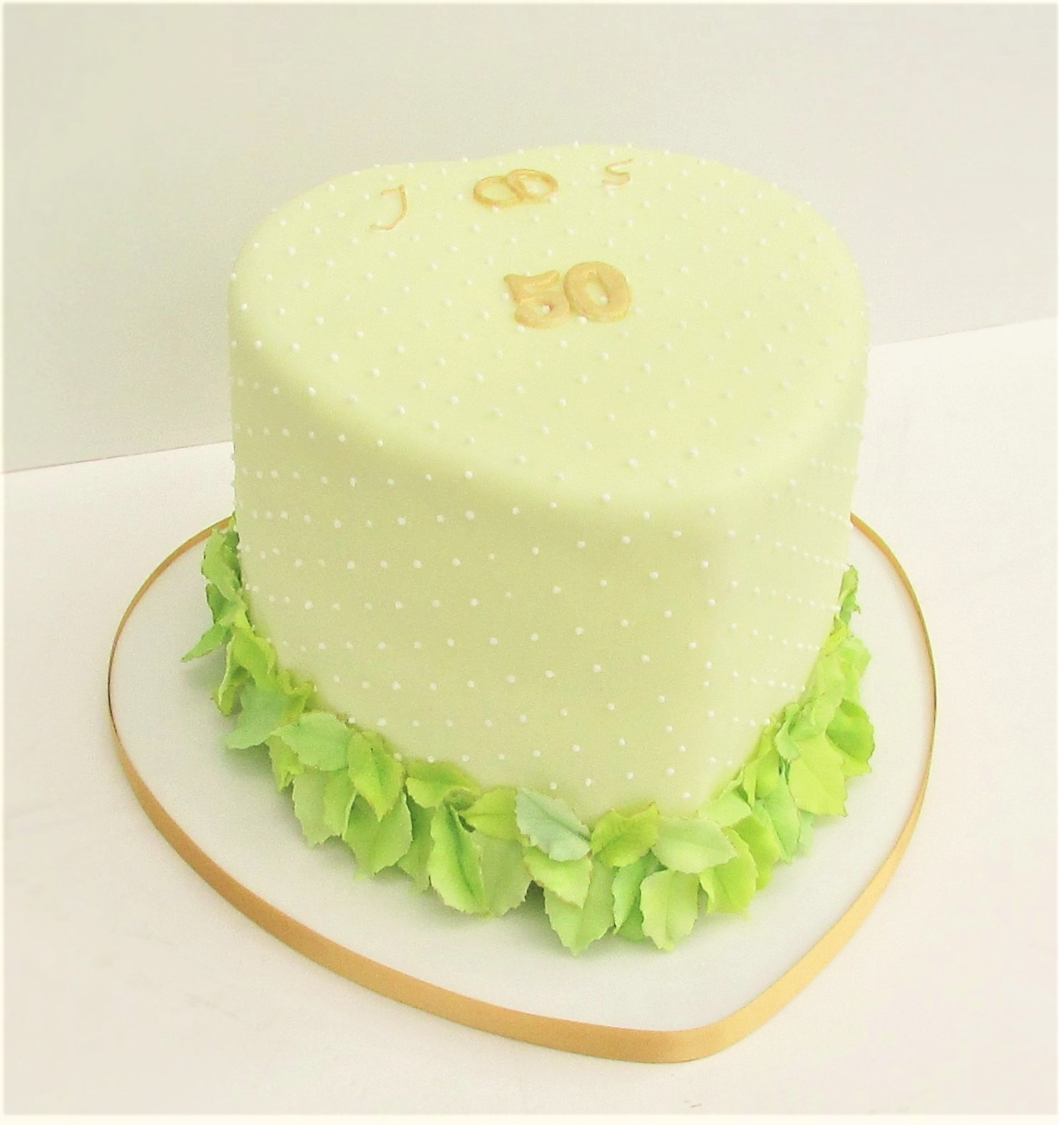 Yellow heart party cake with dots and leaves