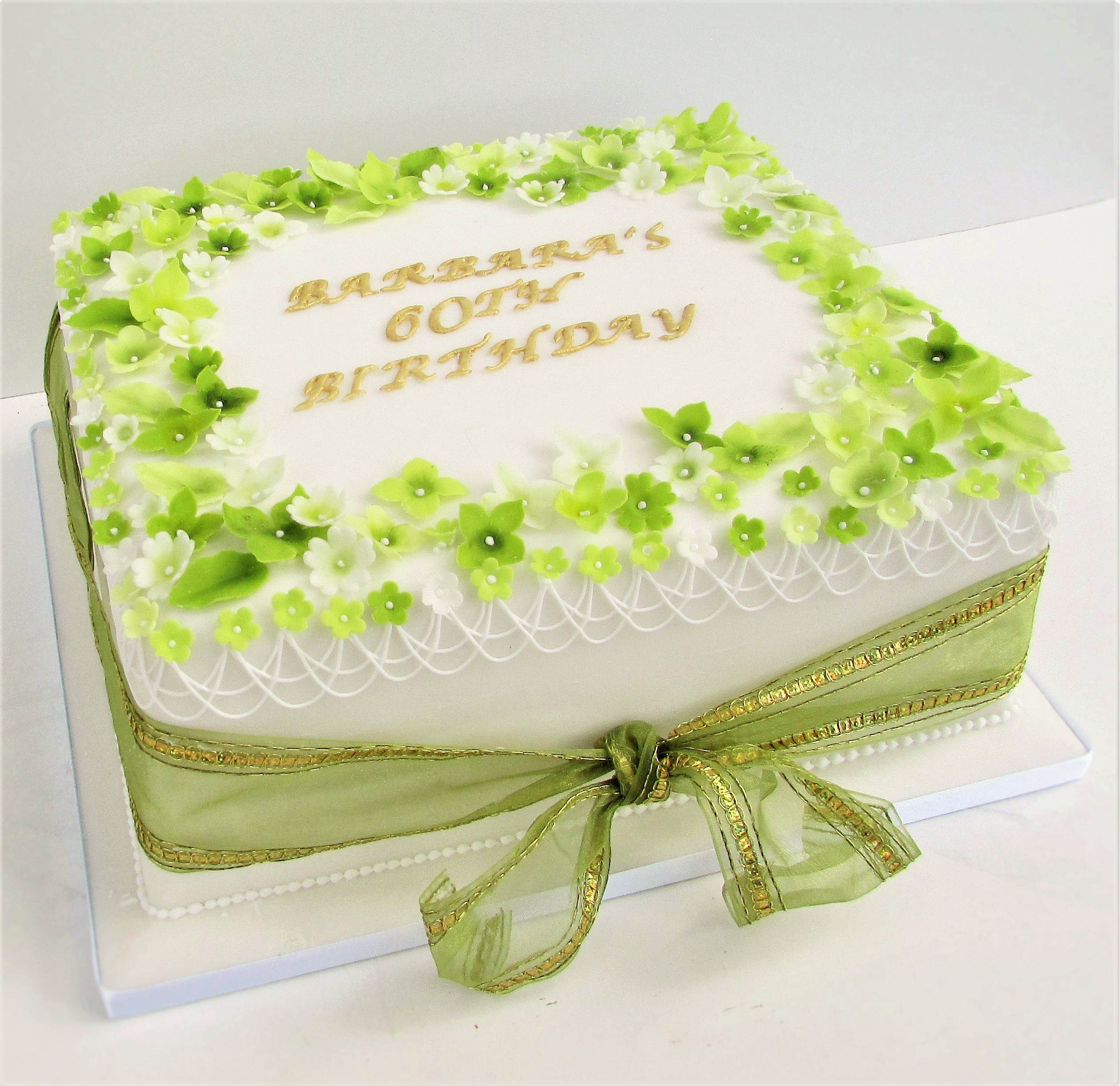 White party cake decorated with green sugar blossoms
