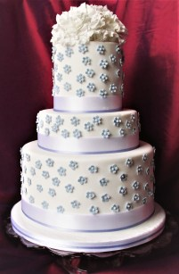 Tiered wedding cake with blue blossoms and sugar peonies