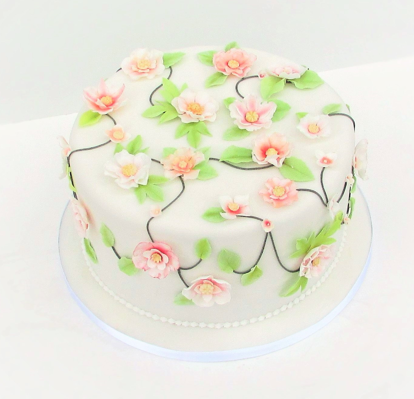 White party cake with pale pink flowers and green leaves