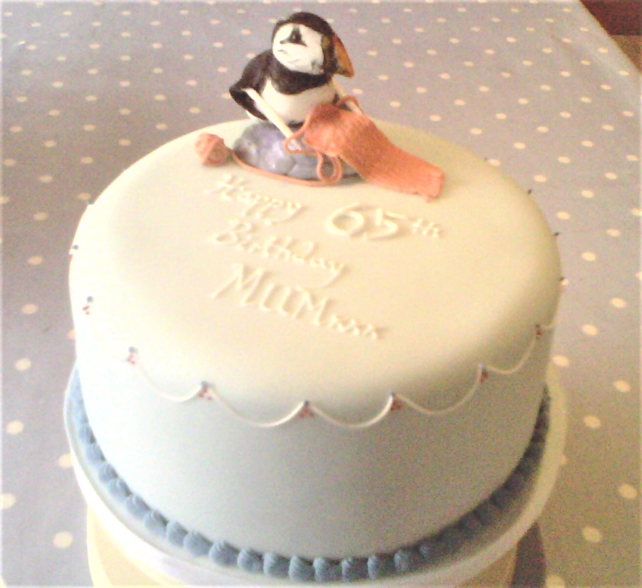 Blue party cake with a sugar puffin on top knitting