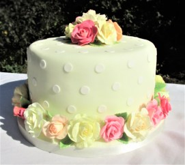 Yellow and white dotty party cake with sugar roses