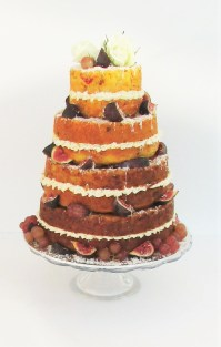 Tiered naked savoury wedding cake with fruits and roses
