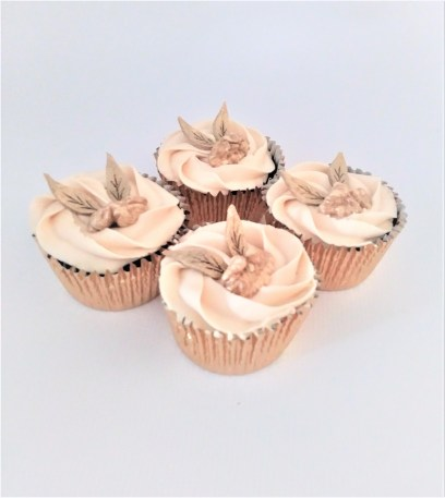 A photograph of Walnut, Cheddar & Apple Cupcakes with Marsala Cheese Cream & Gold Dusted Walnut & Apple Leather Leaf Decoration