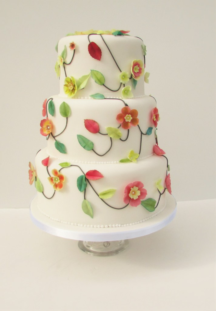 Tiered white wedding cake with applique leaves and flowers in oranges, yellows and greens