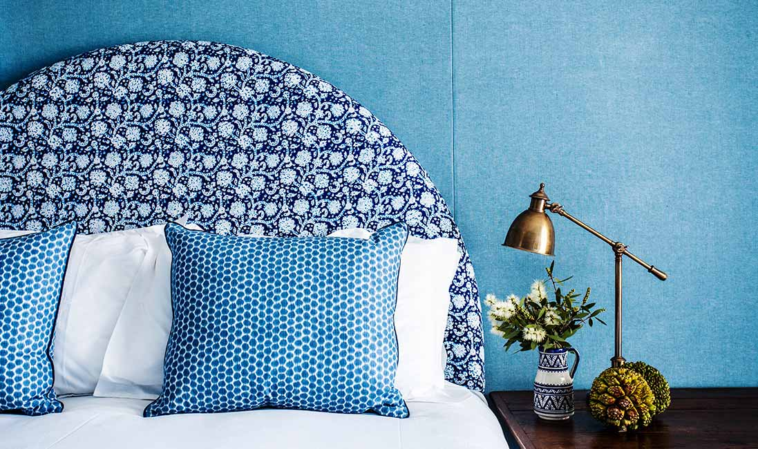 blue-upholstered-wall-print-headboard-pillows-cococozy-halcyonhouse