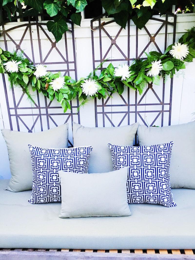 summer outdoor wine bar bench cococozy pillows green white flower garland