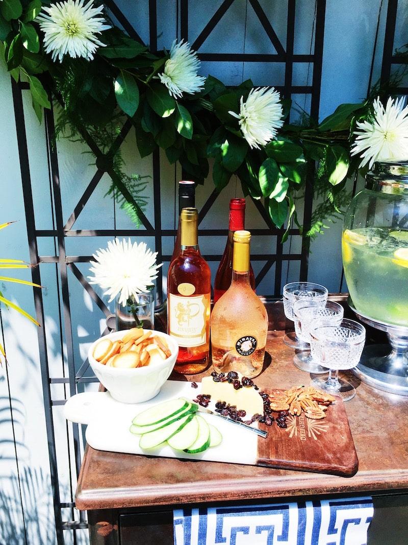 Summer outdoor wine bar cheese board rose flower garland