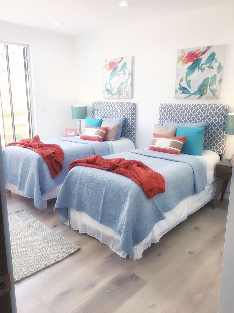 two-twin-bedrooms-blue-red-wood-floors-rug