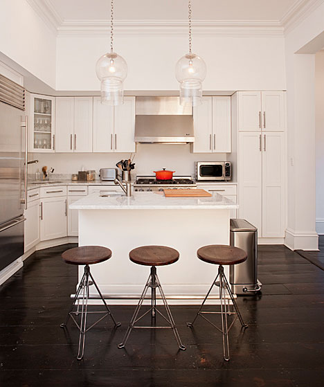 Kitchen with dark wood floor, stainless appliances, white cabinets and drawers, two pendant lights and three bar stools with leather seats