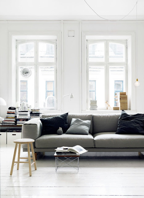 living room with a gray sofa with gray and black acecnt pillows, a side table full of books, a stool being use as a tiny coffee table and tall windows