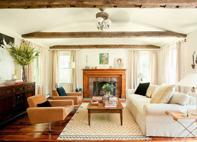 Living room in a farmhouse with exposed beam ceiling, a fireplace with a wood mantel, wood floor, a long white sofa, a reclaimed wood coffee table and two modern burnt orange armchairs