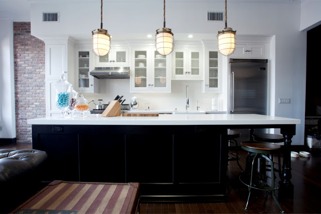Kitchen in Daniel Lowe's Hollywood loft with three large pendant lights, dark black island, quartz counter tops, white kitchen cabinets, bar stools, wood florring, and a brick wall