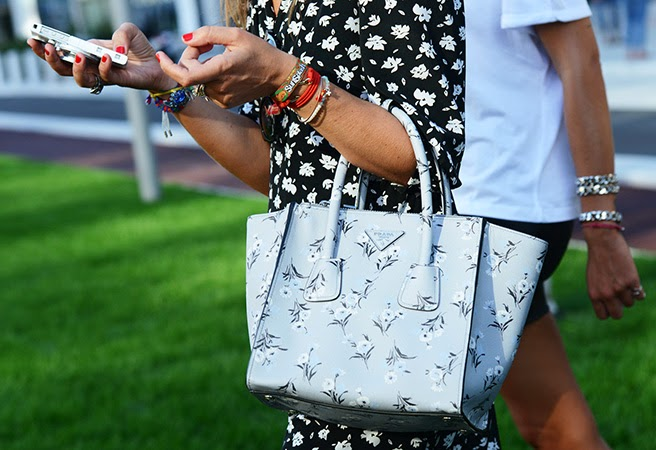 Street style photo of a woman in  floral print dress holding a blue Prada floral saffiano purse