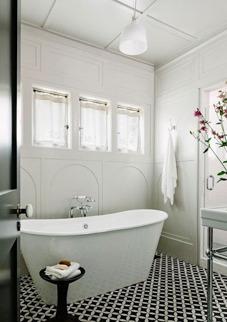 Small bathroom with black and white cement tiles, stand alone tube and white pendant light
