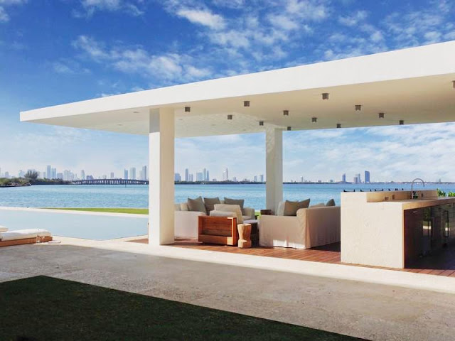 view of Miami skyline from the outdoor bar lounge area with white sofas and wood floor