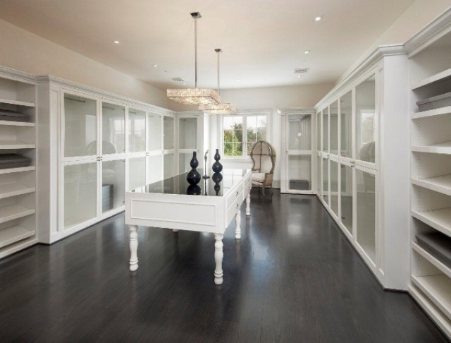 White built in shelves square crystal pendant light white cabinets with glass fronts wood floor walk in closet mansion