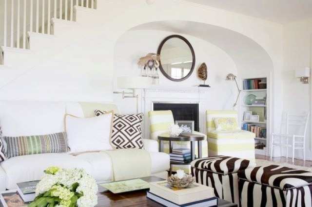 beach cottage with chic zebra ottoman, white sofa, upholstered striped chairs, fireplace with a round mirror on the mantel, and a tortoise shell