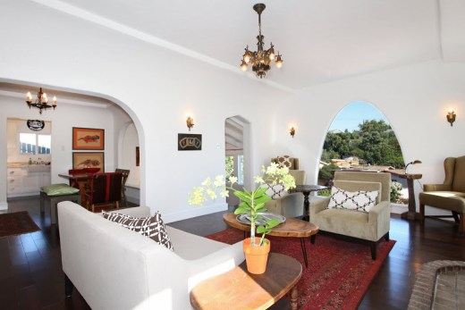 Open living plan in a Spanish Style home with an arched picture window, club chairs and a grey sofa with cococozy pillows and throws, dark wood floors, a red Moroccan rug, a brick fireplace and a chandelier