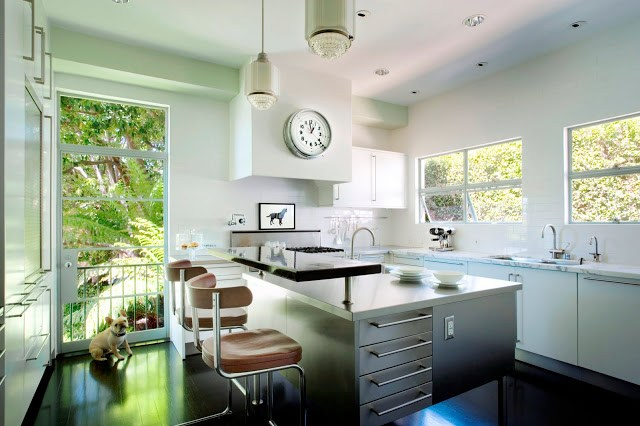 Kitchen from Kitchens and Baths by Michael S. Smith with stainless island with long drawer pulls, a black floor, white cabinets, two pendant lights and stainless appliances