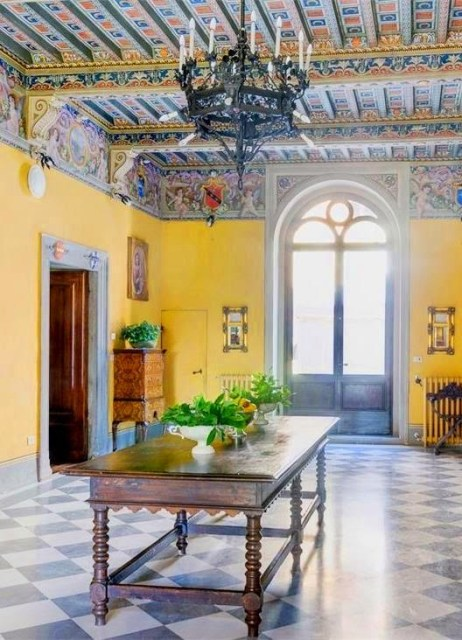Room in Castello di Modanella with painted ceiling and yellow walls in Tuscany